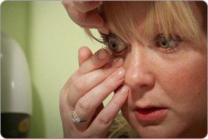 Dame som setter inn en kontaktlinse